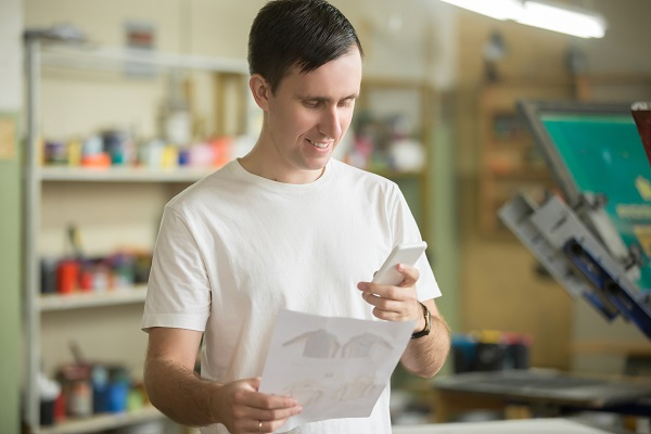 Lifestyle portrait of attractive young man holding cell phone, having effectively discussed with customer or partner art prints for commercial applications. Small business owner in silkscreen workshop